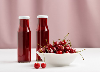 Cherries in a bowl and two bottles of cherry juice.