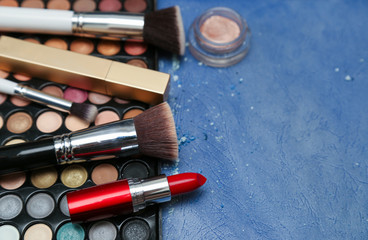 Collection of makeup products on blue background with copyspace