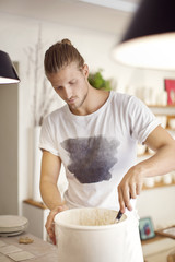 Young male worker working in crockery workshop