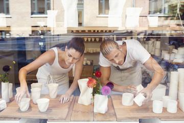 Young woman and man arranging ceramics on window display
