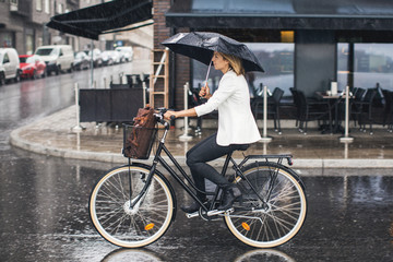 Businesswoman riding bicycle on wet city street during rainy season