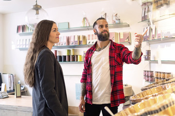 Owner showing products to customer in candy store