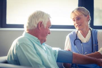 Female doctor checking blood pressure of senior man