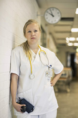 Thoughtful female doctor leaning on wall in hospital