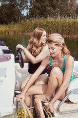 Young female friends traveling by motorboat