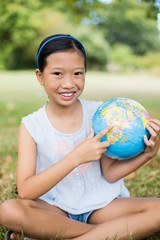 Portrait of smiling girl pointing at globe