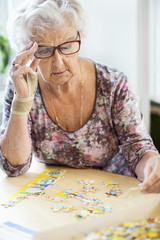 Senior woman solving jigsaw puzzle at table in nursing home