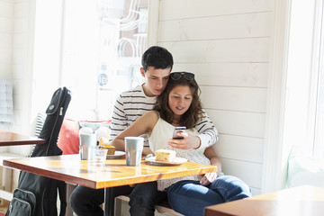 Loving couple using mobile phone at restaurant