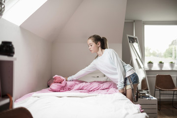 Girl making bed in room