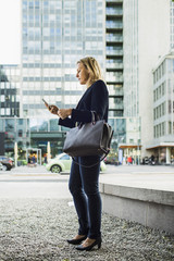 Full length side view of businesswoman using mobile phone on city sidewalk