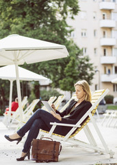 Full length of businesswoman using digital tablet on lounge chair at park