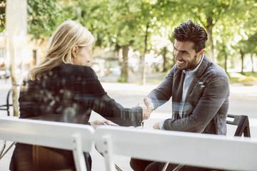 Business partners shaking hands at sidewalk cafe