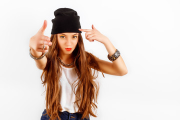beautiful woman wearing in black hat and white T-shirt standing near white wall, shows the gun fingers of hands