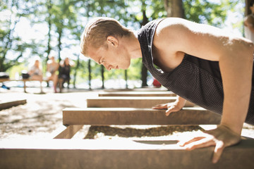 Side view of man doing push-ups at outdoor gym