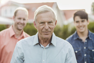 Portrait of confident senior man with son and grandson standing in yard