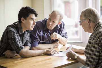 Family discussing over documents at table
