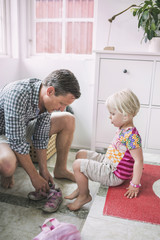 Father assisting daughter in putting shoes at home