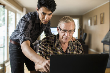 Grandson assisting grandfather in using laptop at home