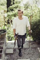 Full length of happy man with gardening equipment walking at yard
