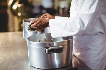 Mid section of chef holding cooking pot