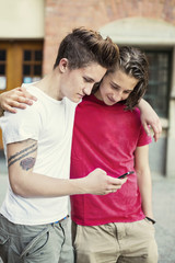 Male friends reading text message on mobile phone at high school schoolyard
