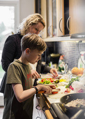 Son and mother cutting vegetables in kitchen