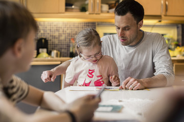 Father teaching daughter with son in foreground at home