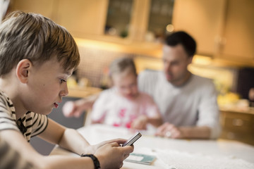 Side view of boy using mobile phone with sister and father in background at home