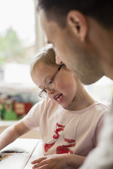 Girl with down syndrome studying by father at home