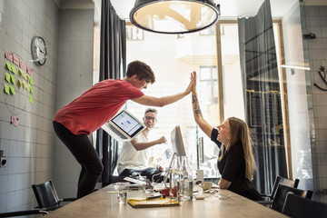 Young people giving high five in creative office