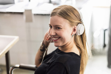 Smiling young businesswoman wearing headphones in creative office