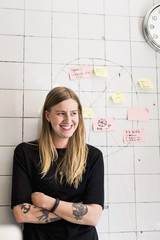 Smiling young businesswoman standing in front on wall with sticky notes in new office