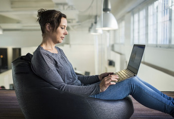 Side view of mature businesswoman using laptop while sitting on bean bag in office