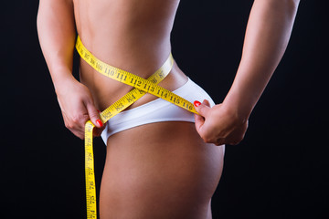 Woman measuring her slim body isolated on black background