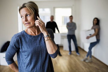 Mature woman using mobile phone while family carrying moving boxes in background at home