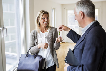 Happy male real estate agent giving keys to woman in new house