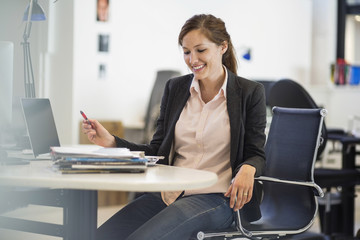 Smiling businesswoman working at desk in office