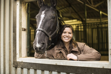 Portrait of happy young woman with horse in stable