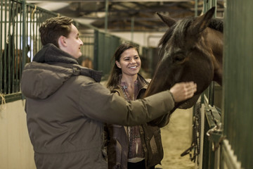 Happy young couple stroking horse in stable