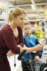Mother and son checking shopping list in grocery store