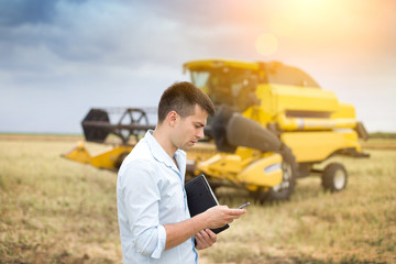 Businessman with laptop and cell phone in front of combine harve