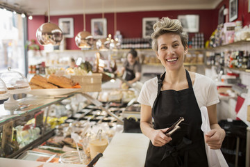 Portrait of happy saleswoman cutting cheese at counter in supermarket