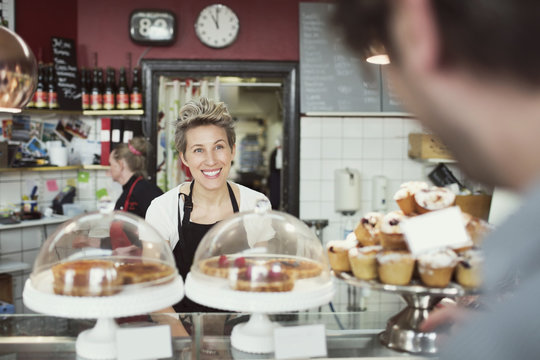 Smiling saleswoman attending customer in supermarket