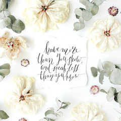 "quote ""have more than you show and speak less than you know"" written in calligraphy style on paper with pink, red roses, ranunculus, white flowers and leaves isolated on white background. Flat lay"