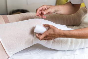 Terapista che esegue il bendaggio  elastocompressivo su arti inferiori con problemi di edema linfatico