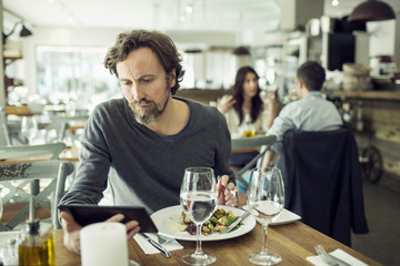 Mature man using digital tablet in restaurant