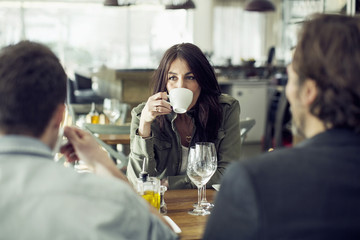 Mature woman drinking coffee while looking at colleague during lunch meeting in restaurant