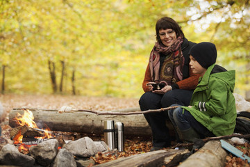 Mother and son roasting marshmallows while camping in forest