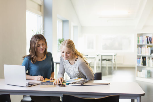 Teenage girls using mobile phone at table in school library