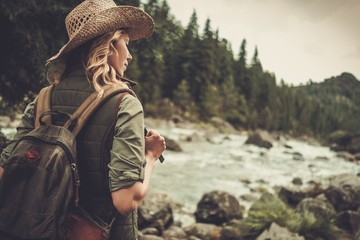 Beautiful woman hiker enjoying amazing landscapes near wild mountain river. Wall mural